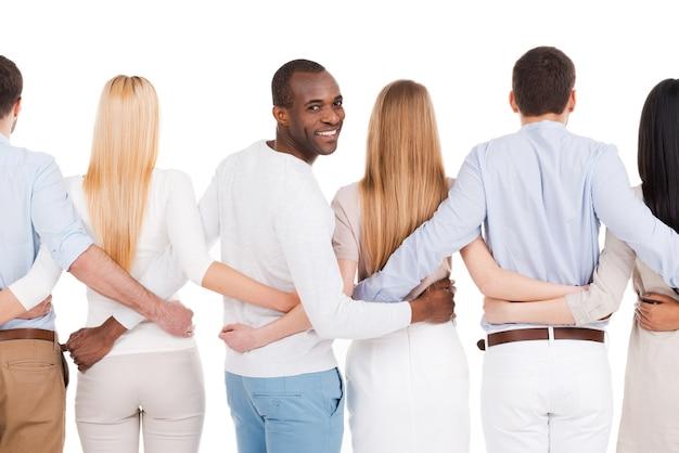 Ensemble, nous sommes plus forts ! vue arrière d'un groupe de personnes diverses se liant les unes aux autres et debout sur un fond blanc tandis qu'un homme africain regarde par-dessus l'épaule et sourit
