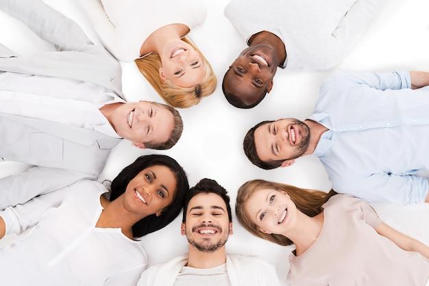 Ensemble, nous sommes plus forts. vue de dessus d'un groupe joyeux de personnes multiethniques allongées sur le dos et souriantes debout isolées sur blanc