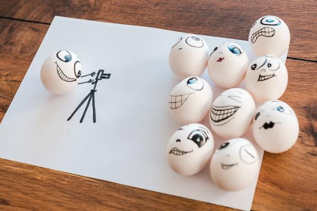 Ensemble, nous sommes plus forts. vue de dessus d'un œuf amusant photographiant ses amis d'œufs pendant qu'ils sont tous allongés sur le morceau de papier et sur le bureau en bois