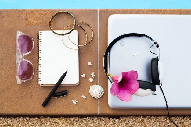Un ensemble d'objets de voyage pigiste hipster portant à la piscine, style été femme, un ordinateur portable, un casque, des bracelets, un carnet de voyage, un stylo, des lunettes de soleil, vue d'en haut, flatlay