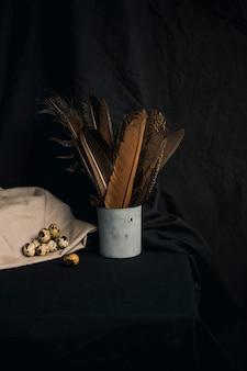 Ensemble d'oeufs de caille sur la serviette près des plumes en boîte