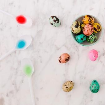 Ensemble d'oeufs de pâques de caille colorée dans un bol près de cuillère avec des colorants