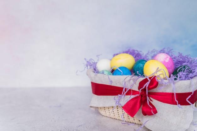 Ensemble d'oeufs de pâques dans un panier décoré