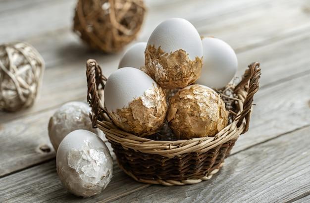 Ensemble d'oeufs de pâques festifs dans un panier en osier sur une table floue. concept de vacances de pâques.