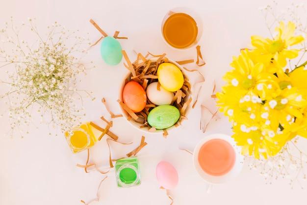 Ensemble d'oeufs de pâques lumineux dans un bol entre des fleurs fraîches et des bidons de liquide colorant