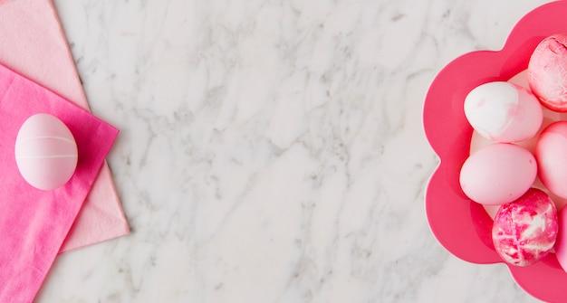 Ensemble d'oeufs de pâques roses sur assiette et serviettes