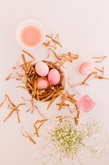 Ensemble d'oeufs de pâques roses dans un bol entre les fleurs et les boîtes de conserve de liquide de teinture