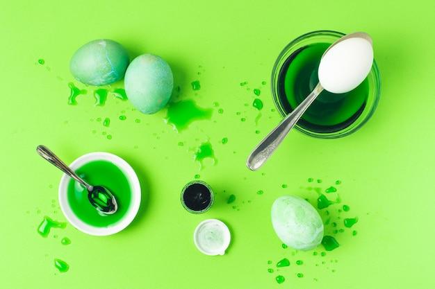 Ensemble d'oeufs de pâques verts entre les taches, la cuillère et le liquide colorant