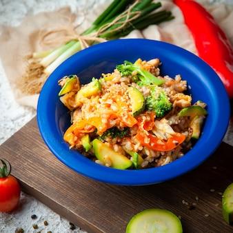 Ensemble d'oignons verts et de poivre et de délicieux repas dans une assiette bleue sur un bois, un tissu rouge et un fond texturé blanc. vue grand angle.