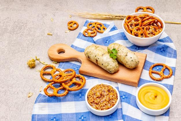 Ensemble oktoberfest. weisswurst saucisse blanche, bretzels, moutarde, épillets de grain, houblon