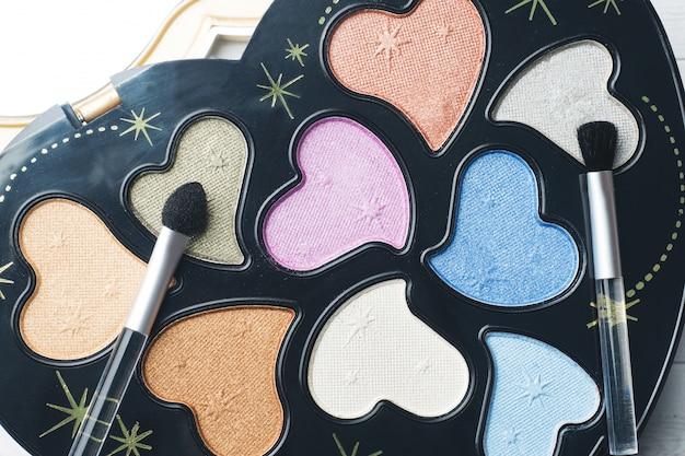 Un ensemble d'ombres à paupières colorées et de pinceaux de maquillage. mise au point sélective.