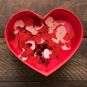 Ensemble d'ornement petits coeurs colorés dans la boîte présente