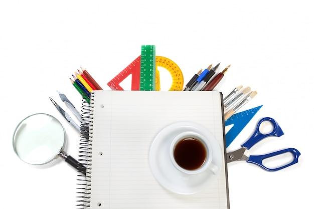 Un ensemble d'outils de bureau sur le cahier pour des notes et une tasse de café. sur un mur blanc.
