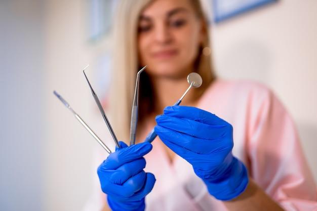 Ensemble d'outils dentaires dans les mains. miroir buccal, détartreur parodontal, pince à extraction dentaire, pince, ciseaux
