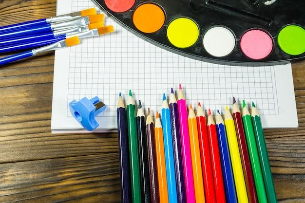 Ensemble d'outils de dessin sur fond en bois. cahier vierge, peintures à l'aquarelle, pinceaux, crayons de couleur sur le bureau