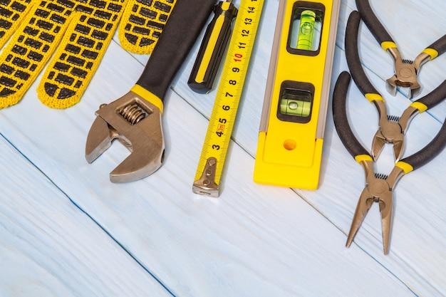 Ensemble d'outils et de gants de travail sur des tableaux bleus