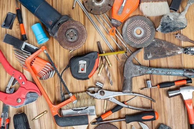 Ensemble d'outils manuels, situé sur un plancher en bois.