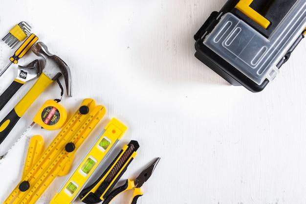 Ensemble d'outils de menuiserie jaune avec boîte à outils en plastique sur fond blanc