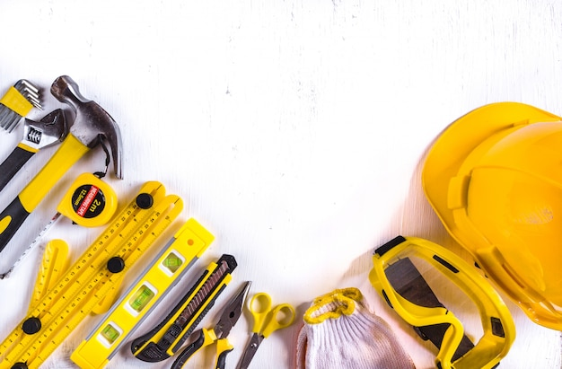 Ensemble d'outils de menuiserie jaune avec équipement de sécurité de construction standard sur fond blanc