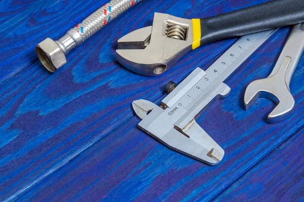 Ensemble d'outils nécessaires pour les plombiers et les tuyaux sur les planches en bois bleu avec espace pour la publicité