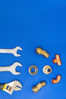 Ensemble d'outils et de pièces détachées pour la plomberie isolé sur un espace bleu avec un espace pour la publicité