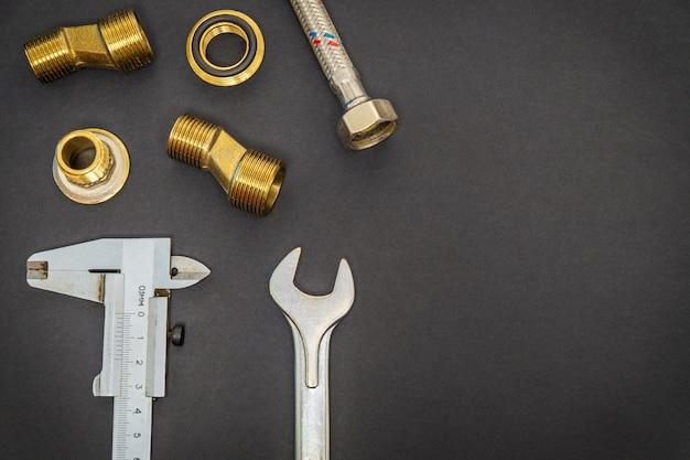 Ensemble d'outils et de pièces de rechange pour la plomberie sur un espace noir avec un espace pour la publicité