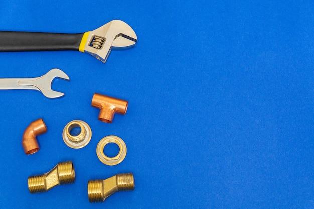 Ensemble d'outils pour la plomberie isolé sur un espace bleu avec un espace pour la publicité