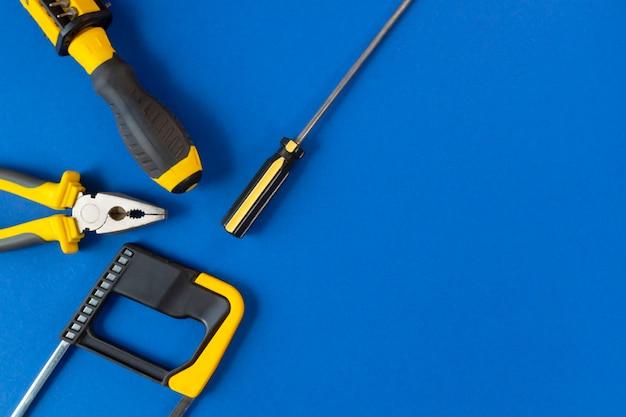 Un ensemble d'outils de réparation isolé sur un mur bleu
