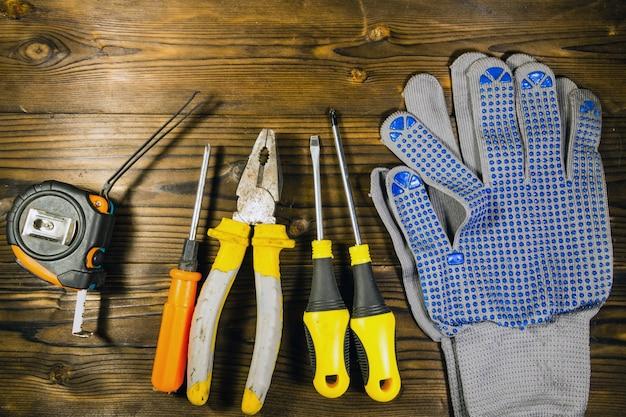 Ensemble d'outils de travail sur fond en bois. tournevis, ruban à mesurer, pinces et gants sur la surface du bois