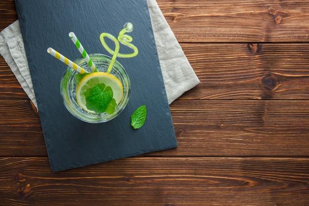 Ensemble de paille, chiffon blanc et tranches de citron dans un bol sur un fond en bois. vue de dessus. copier l'espace pour le texte