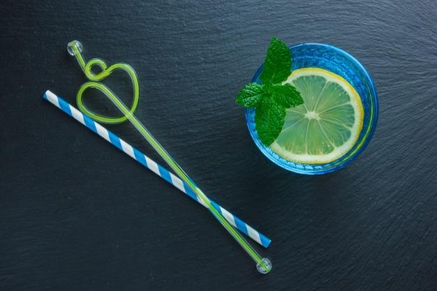 Ensemble de pailles et tranche de citron dans un bol bleu sur une surface en pierre sombre. vue de dessus.