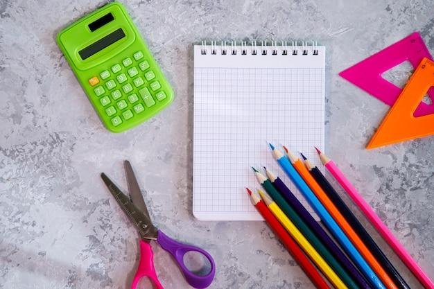 Un ensemble de papeterie, calculatrice, cahier, crayons de couleur, règles, ciseaux