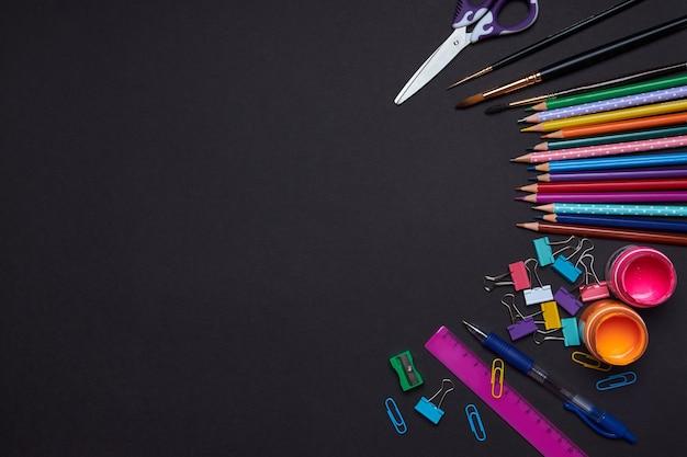 Ensemble de papeterie scolaire pour enfants à étudier. peinture stylo crayon règle trombone sur fond de papier noir