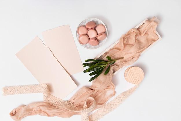 Ensemble de papier et macarons sur une assiette près de textile