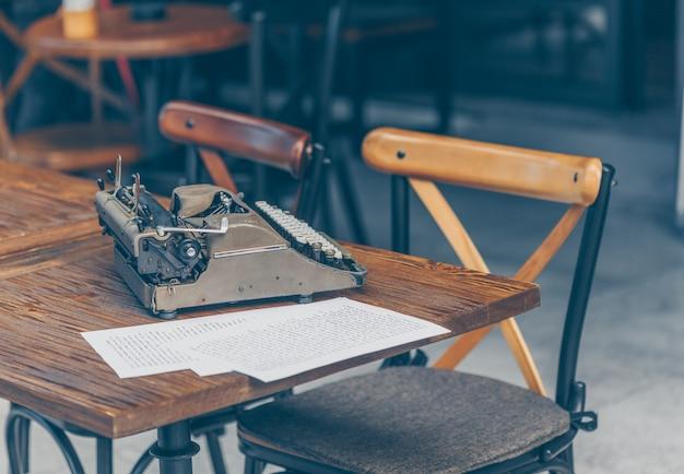 Ensemble de papiers et machine à écrire sur table en terrasse de café, vue latérale.