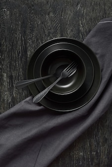 Ensemble à partir d'assiettes en céramique de couleurs noires servies avec une cuillère et une fourchette et une serviette ou une serviette en textile sur le même fond de pierre de couleur, espace de copie. vue de dessus.