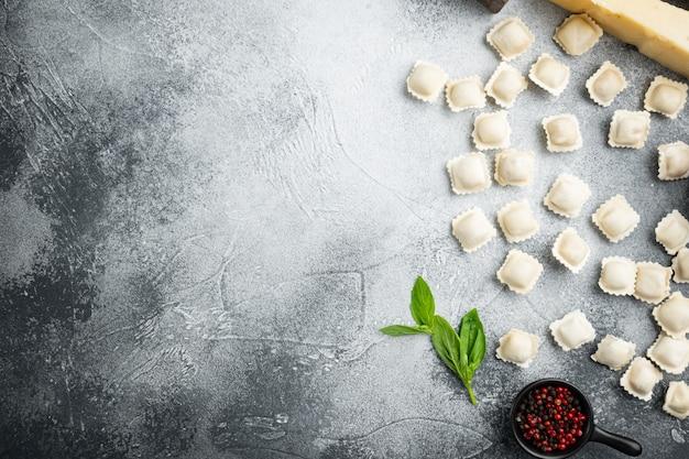 Ensemble de pâtes raviolis italiens frais faits maison, sur fond gris, vue de dessus à plat,