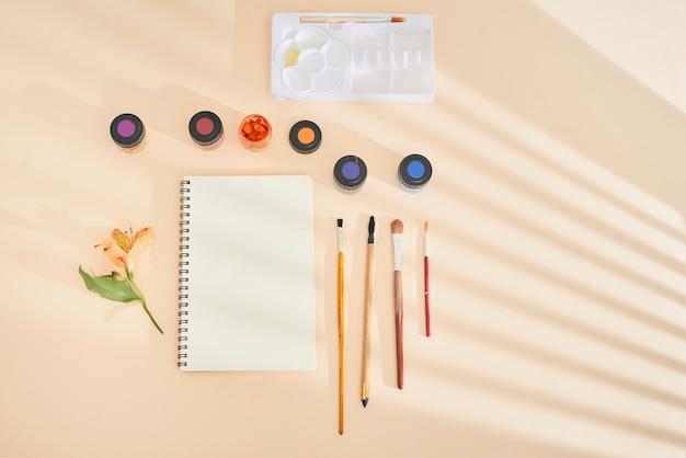 Ensemble de peinture à l'aquarelle, de pinceaux d'art et de papier sur un bureau