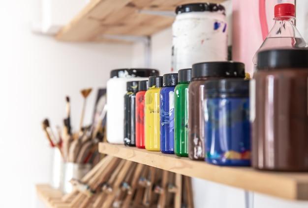 Un ensemble de peintures dans des pots, pour dessiner et peindre sur une étagère dans un atelier., gros plan, différentes couleurs.