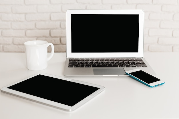 Ensemble de périphériques informatiques modernes avec ordinateur portable, tablette numérique et smartphone se bouchent sur le tableau blanc