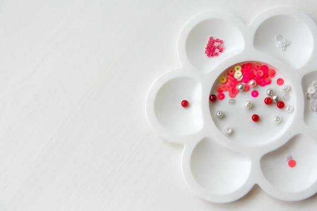Ensemble de perles et de paillettes de couleur blanche, rouge dans un récipient blanc sous la forme d'une fleur sur un fond en bois blanc