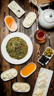 Ensemble de petit-déjeuner composé de fromages, de miel, de thé et d'un kyukyu traditionnel azéri avec grenade