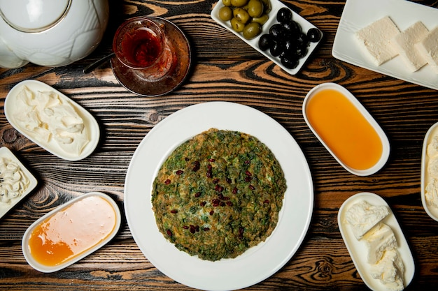 Ensemble de petit-déjeuner composé de fromages, de miel, de thé et d'un kyukyu traditionnel azéri