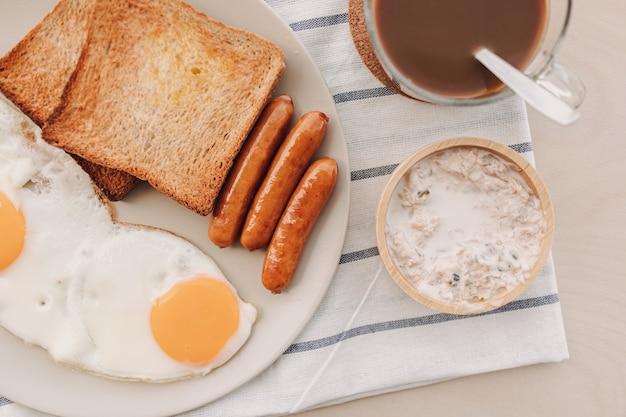 Ensemble de petit-déjeuner composé d'œufs au plat, de saucisses de pain grillées et de pâte de thon