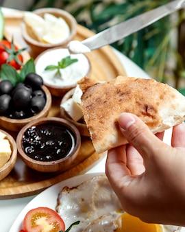 Ensemble petit déjeuner et pain à la main