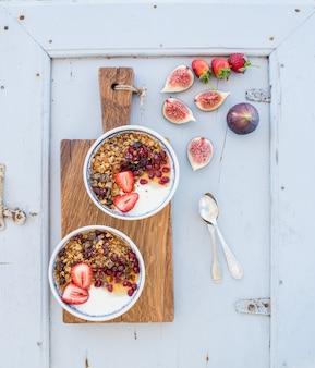 Ensemble petit déjeuner sain. bols de granola d'avoine avec du yaourt, des fraises fraîches, des figues, de la grenade et du miel sur une planche de bois rustique sur bleu clair