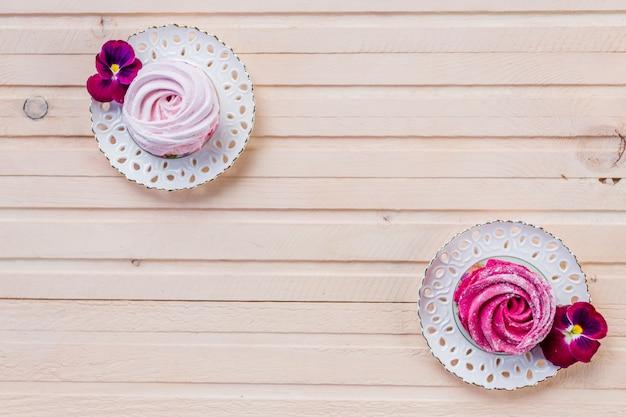 Ensemble de petits gâteaux blancs et roses faits maison sur table en bois