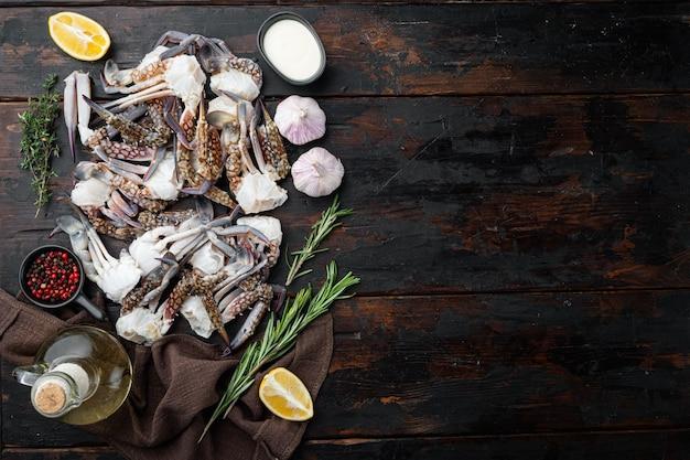 Ensemble de pièces de crabe de fleurs crues fraîches ou de crabe bleu, sur fond de bois foncé, vue de dessus à plat, avec fond et espace pour le texte