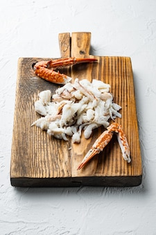 Ensemble de pièces de crabe de natation bleu bouilli, sur une planche à découper en bois, sur fond blanc