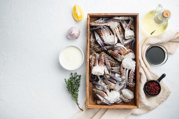 Ensemble de pièces de crabe de natation bleu frais, dans une boîte en bois, sur une table blanche, vue de dessus à plat